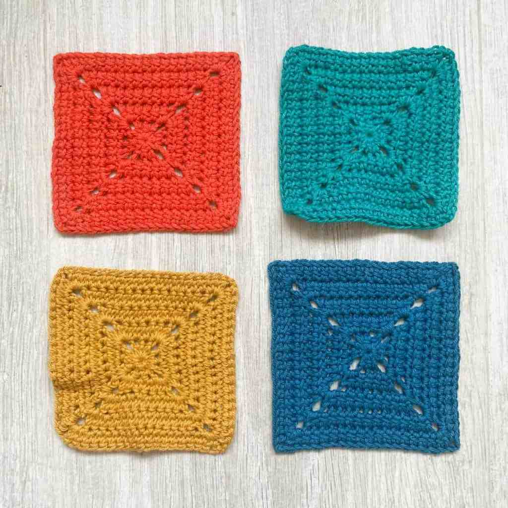 Orange and blue blocked solid granny squares laid next to yellow and turquoise unblocked squares which are a bit ruffled