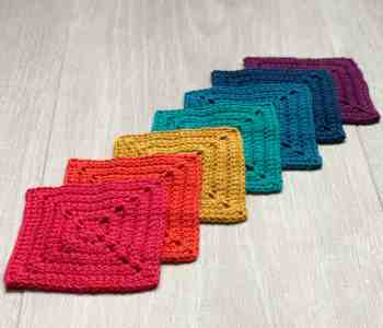 Rainbow coloured crochet granny squares laying flat and overlapping on the diagonal