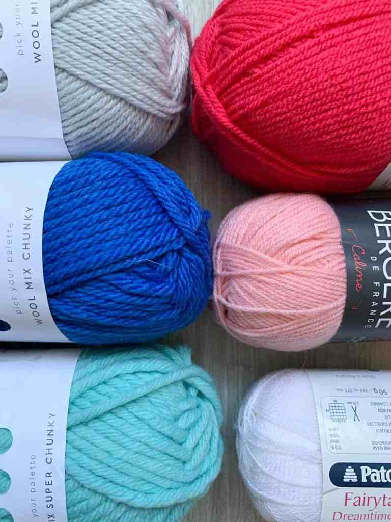 A close up of 6 balls of different weight yarns