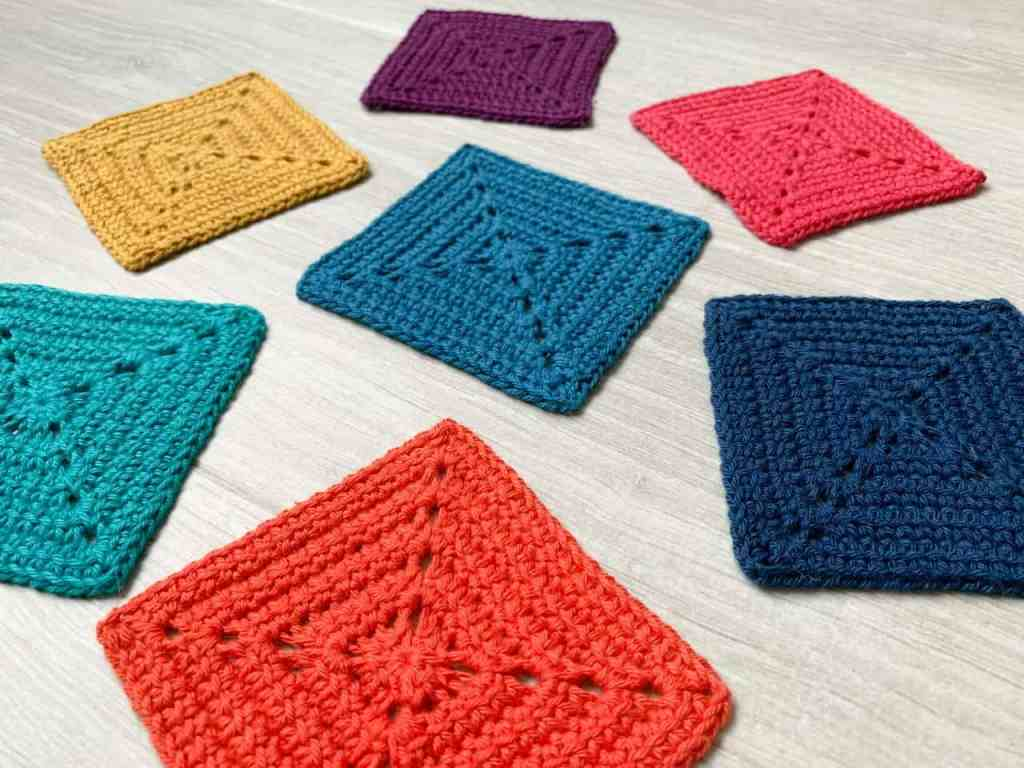 7 rainbow coloured linked double crochet solid granny squares lay scatttered on a grey wood effect surface