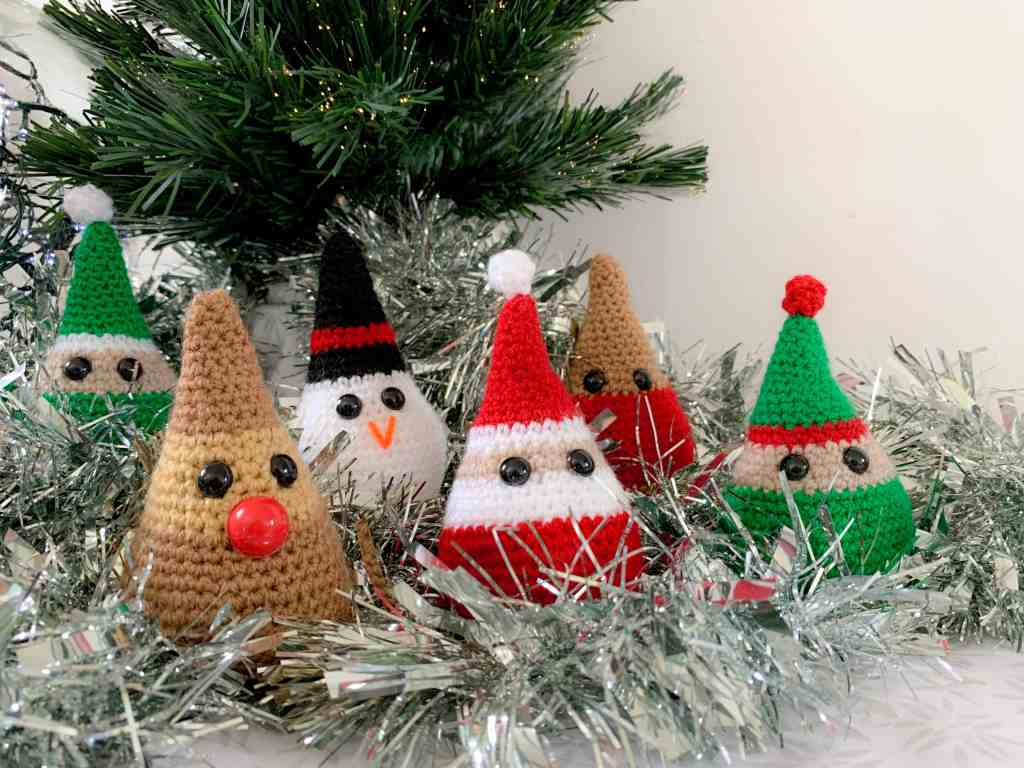 A landscape image of 6 characterful crochet Christmas decorations (Santa, a robin, a reindeer, a snowman and two elves), sit on a white and grey patterned surface in front of the bottom of a Christmas tree with silver tinsel behind it