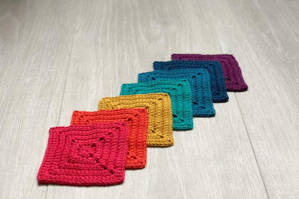 A rainbow of granny squares are laid out overlapping each other in a diagonal line
