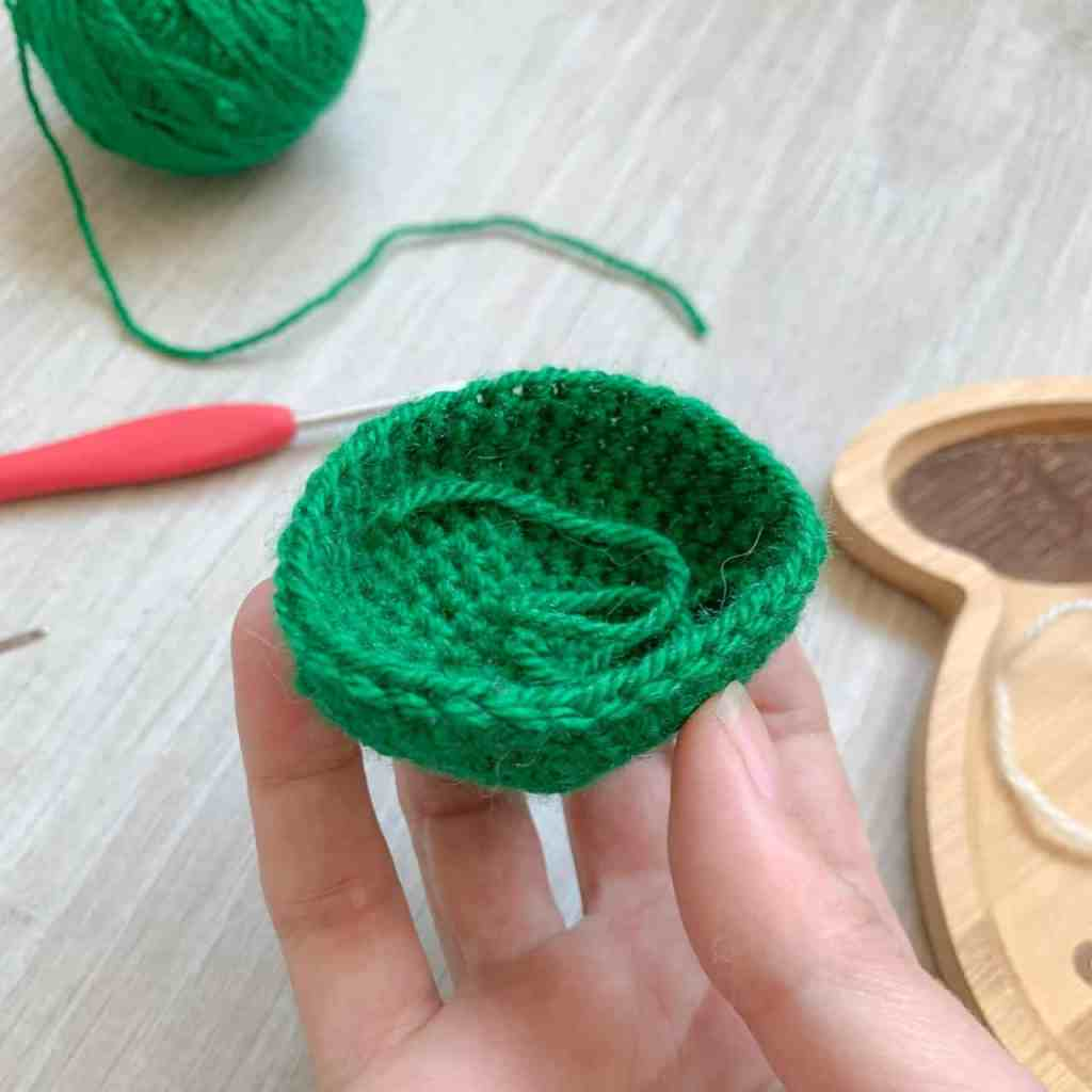 A hand holding a small green bowl shaped crochet project in progress