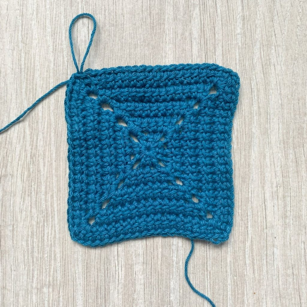 A blue 5 round crochet square motif on a grey wood effect surface
