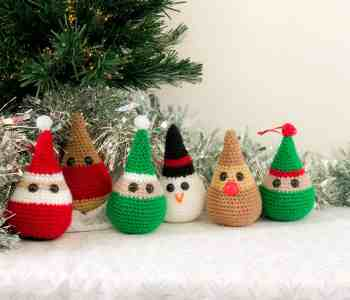 6 crochet character Christmas decorations (Santa, a robin, a reindeer, a snowman and two elves), sit on a white and grey patterned surface in front of the bottom of a Christmas tree with silver tinsel behind it