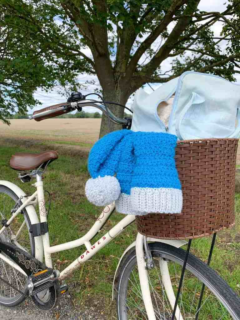 A Dawes Dutchess bike has a crochet hat and cowl hanging out of it's basket