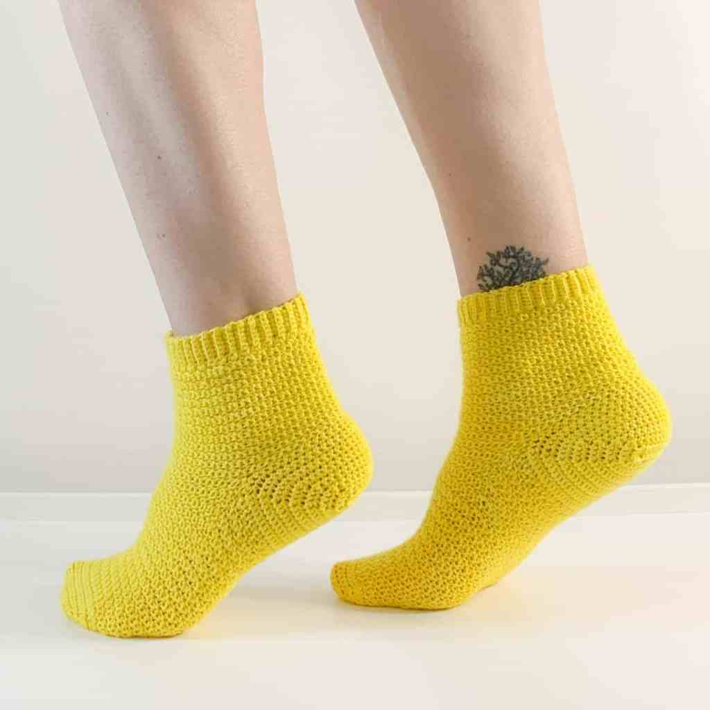 The side view of a woman's feet clad in yellow crochet socks