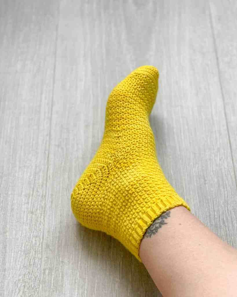A foot wearing a bright yellow crochet sock is shown on a grey wood grain surface