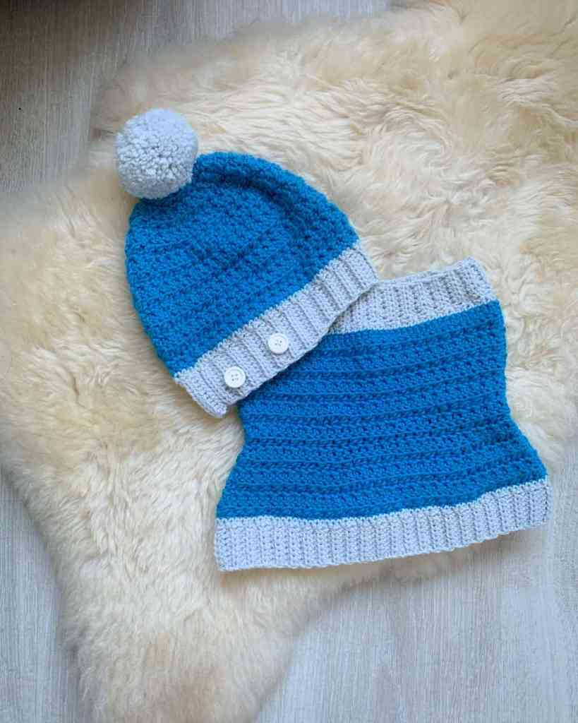 A turquoise and grey hat with a pom pom and buttons and cowl lay on a sheepskin rug