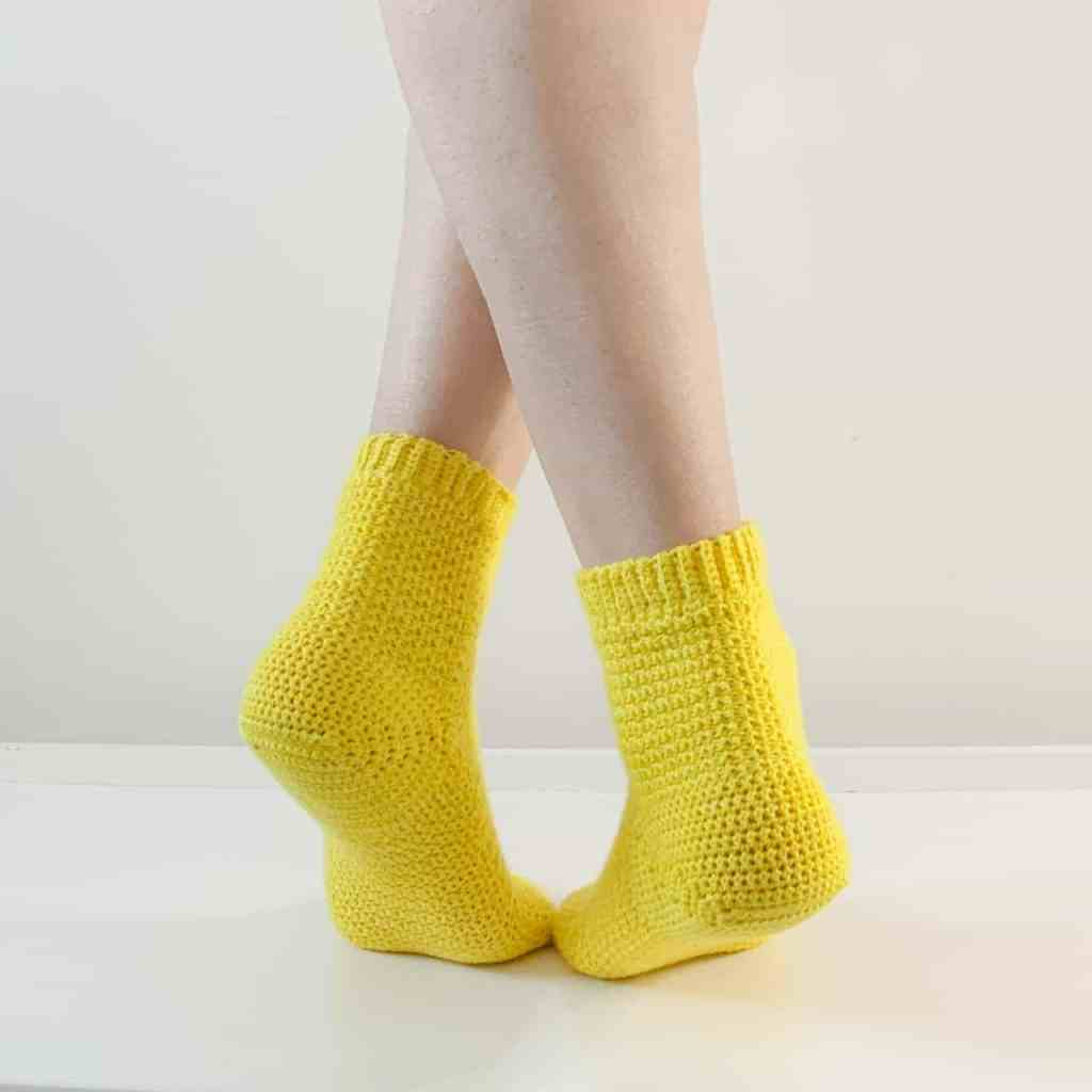 The back of a woman's calves and feet, crossed over wearing yellow crochet socks