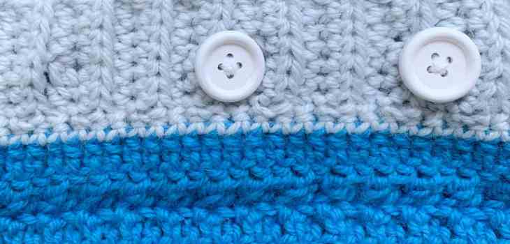 Two pieces of crochet fabric in blue and grey buttoned together with 2 white wooden buttons