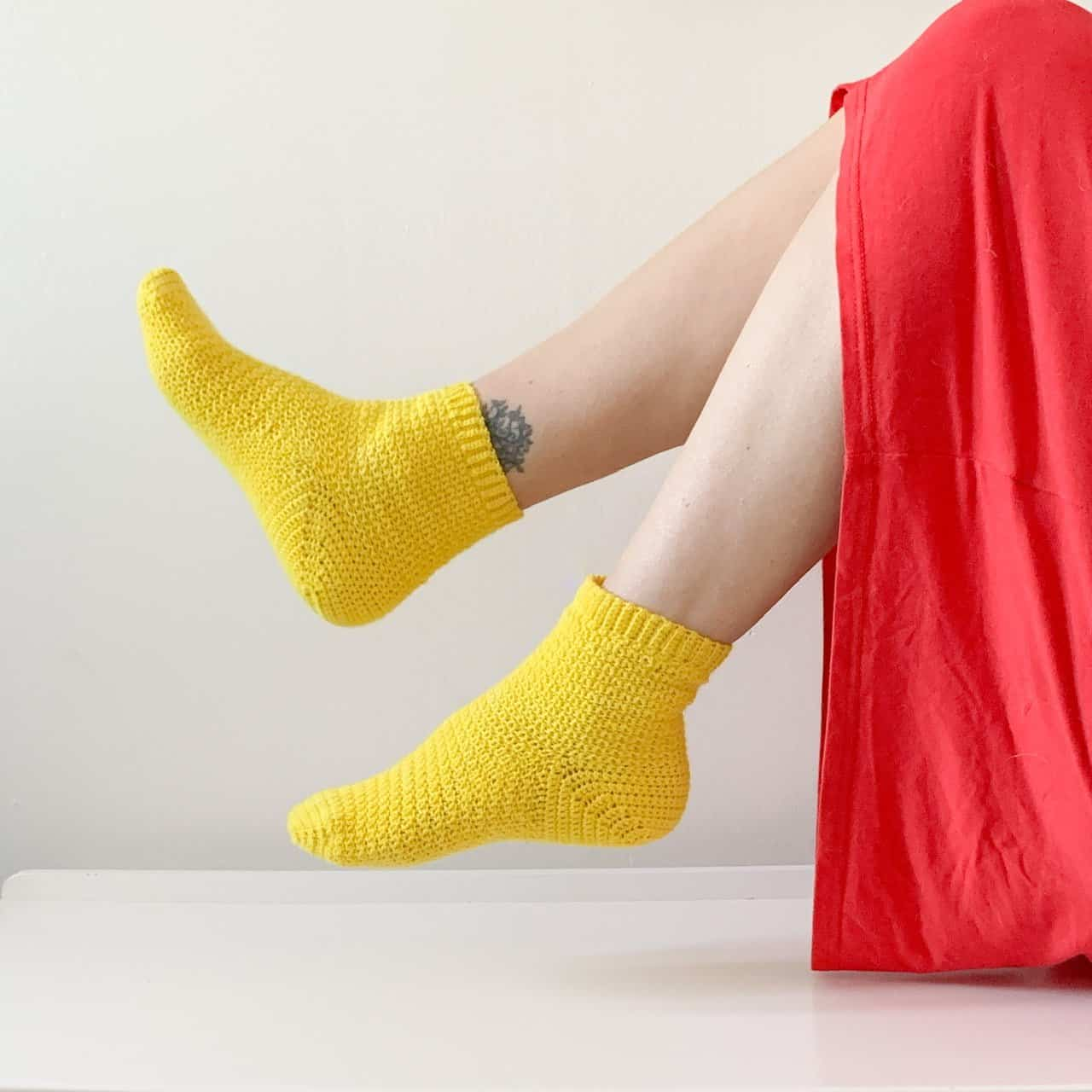 The view of the lower half of a woman in a red dress wearing yellow crochet socks kicking her feet up
