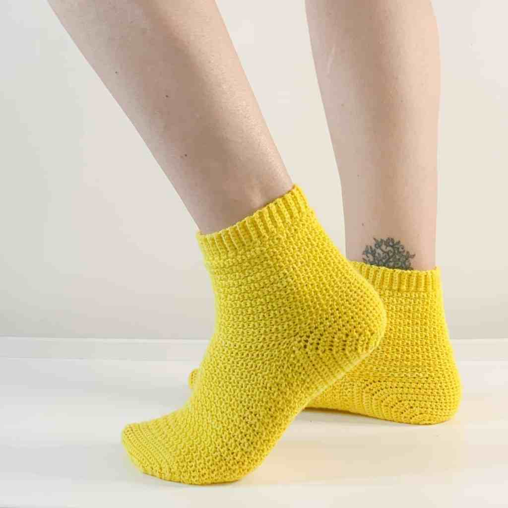 A woman's feet wearing yellow crochet socks on a white surface, the foot closet to the camera is lifted onto tip toes