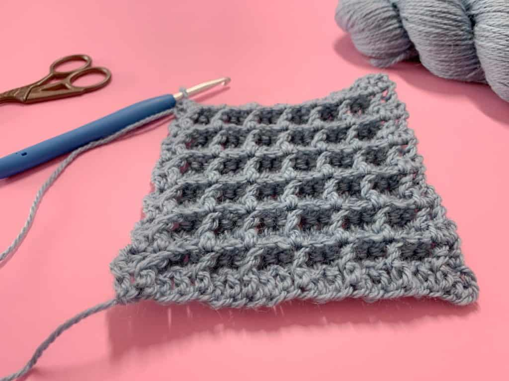 A swatch of crochet waffle stitch in blue-grey yarn with a blue crochet hook attached lies on a pink background with a hank of yarn and pair of scissors to the corner of the frame