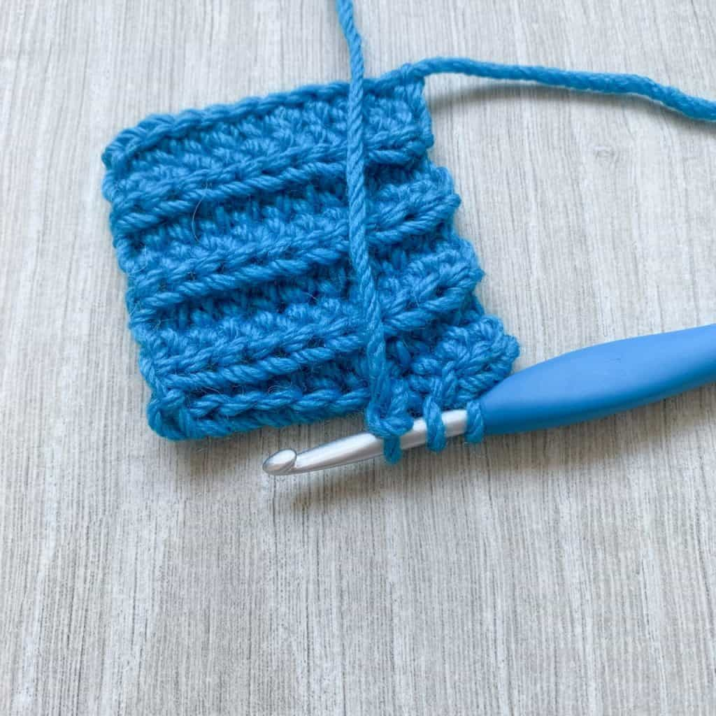 An swatch of crochet ribbing demonstrating the hidden buttonhole technique