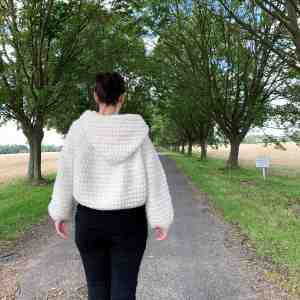 A woman with her back to the camera wearing black jeans and a natural wool crochet hooded cape stands in the centre of a tree lined avenue with fields to either side. Her hands fall by her side
