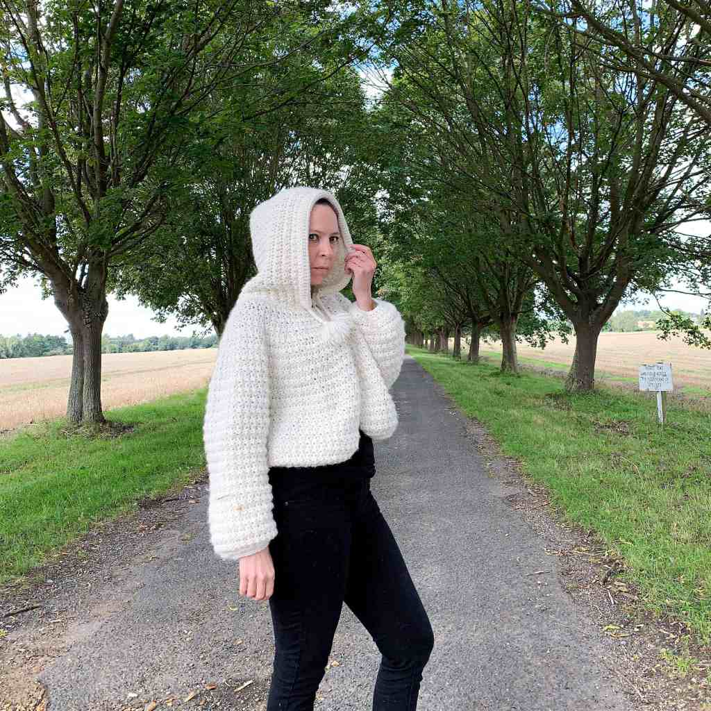 A woman wearing black jeans and a natural wool crochet hooded cape stands in a tree lined avenue with fields to either side. She is holding one side of the hood, standing side on to the camera