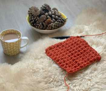 A burnt orange swatch of crochet blanket stitch lies on a sheep skin rug with a bowl filled with pine cones and a cup of tea behind it on a grey wood effect floor. A black crochet hook is still attached to the swatch and barely visible as it sinks into the sheepskin