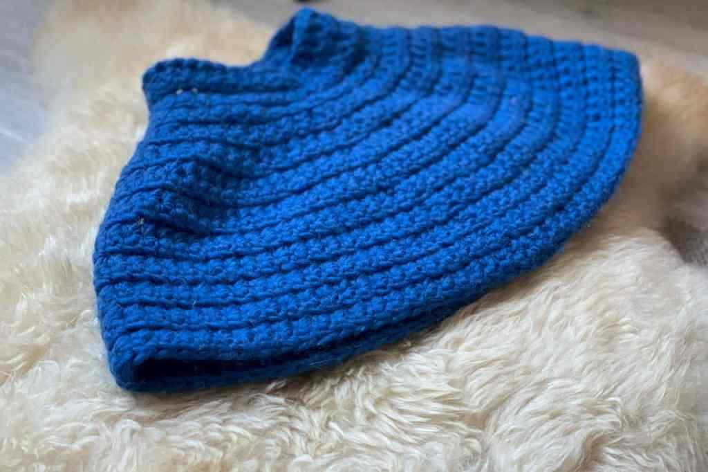 A blue crochet textured caplet lies on a sheepskin rug