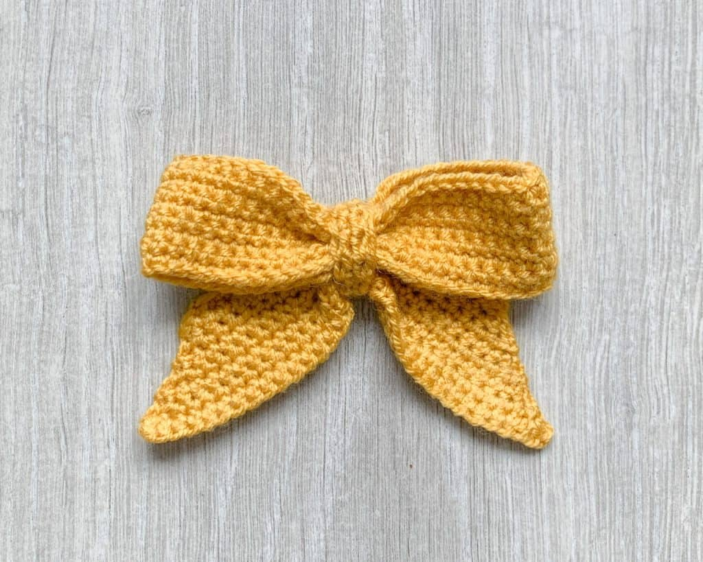 A yellow crochet bow lays on a grey wood effect background