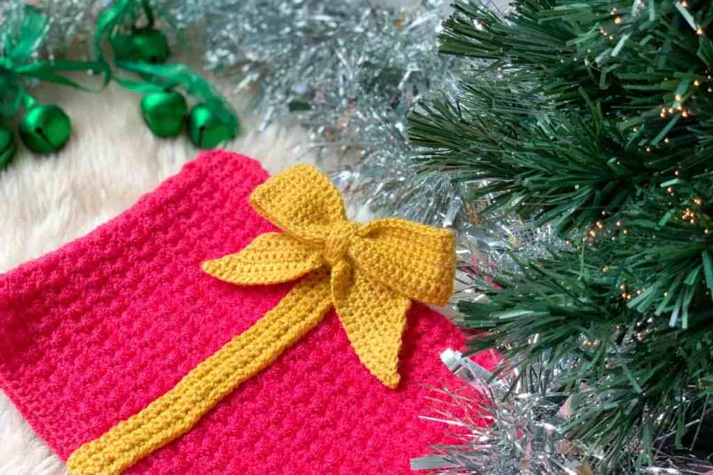 A pink crochet square is adorned with a yellow crochet ribbon and bow and is laying on sheep pelt rug surrounded by tinesel and green bells with the branches of a Christmas tree creeping in to the side of the image