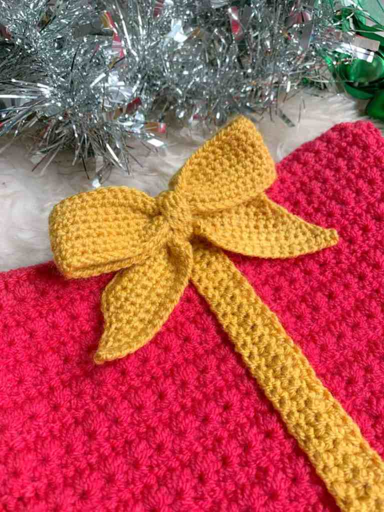 A close up of a pink christmas gift hat with a mustard yellow crochet bow. Tinsel lies behind the hat