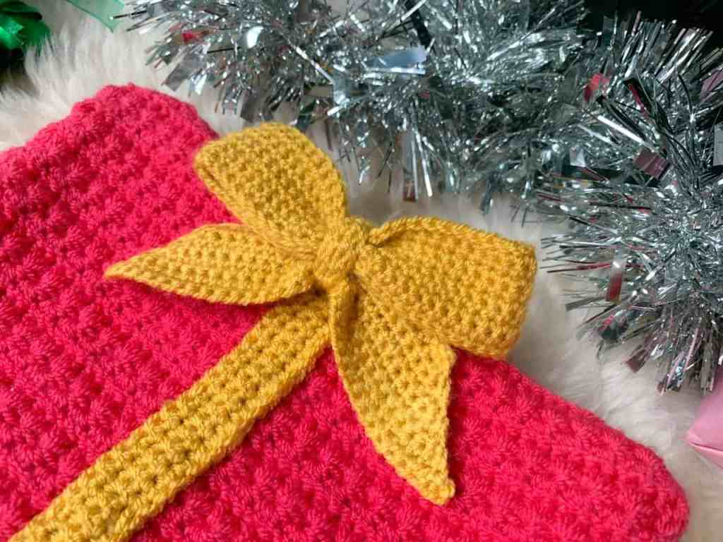 A yellow crochet bow is attached to a pink crochet rectangle surrounded by tinsel, with branches of a christmas tree encroaching