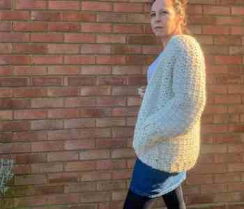 A woman wearing a cream chunky crochet cardigan and a denunciation skirt stands in front of a brick wall, she stands side on to the camera with one hand in the cardigan pocket