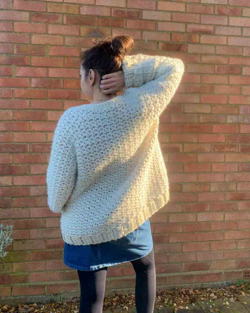 A woman wearing a cream chunky crochet cardigan and a denunciation skirt stands in front of a brick wall, her back is the the camera and her right hand reaches up to tough the back of her neck,. The sun shines from the right.