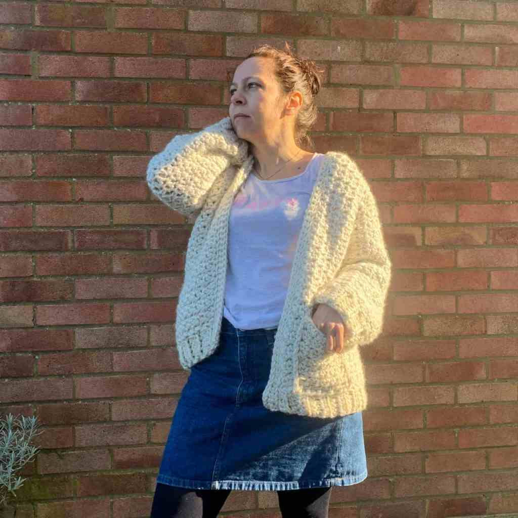 A woman wearing a cream chunky crochet cardigan and a denunciation skirt stands in front of a brick wall, she raises one hand to her head whilst putting the other in the cardigan pocket