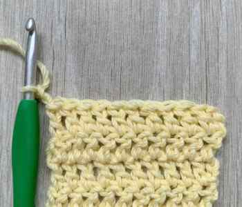 A landscape image of a yellow crochet swatch of double crochet stitches with a green and silver crochet hook still attached