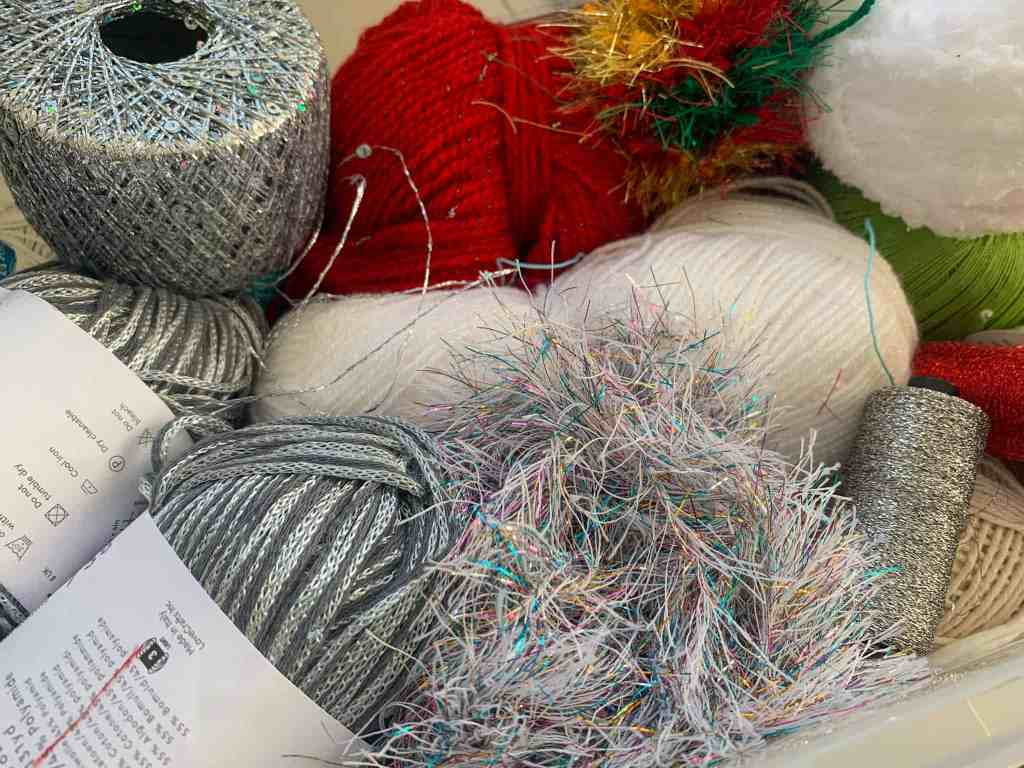 A pile of yarn used for christmas crafts including sequinned yarn, tinsel yarn, metallic, fluff and sparkly yarns in red, white, silver and green