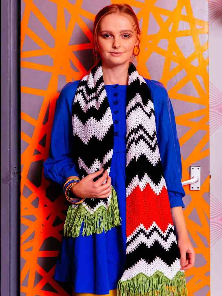 A woman leaning on a door models the black and white mixed signals crochet scarf which has a pop of orange colour and green fringe