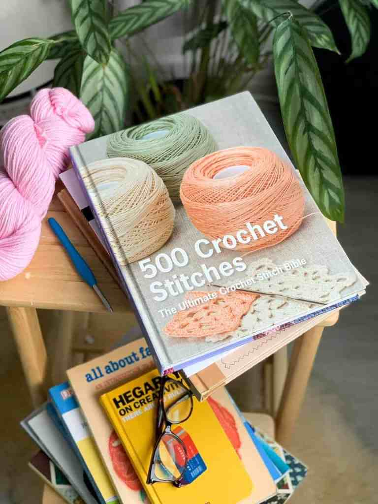 A copy of the 500 Crochet Stitches book sits on top of a wooden stool a top a pile of other crochet books with a hank of pink yarn and a crochet book next to it