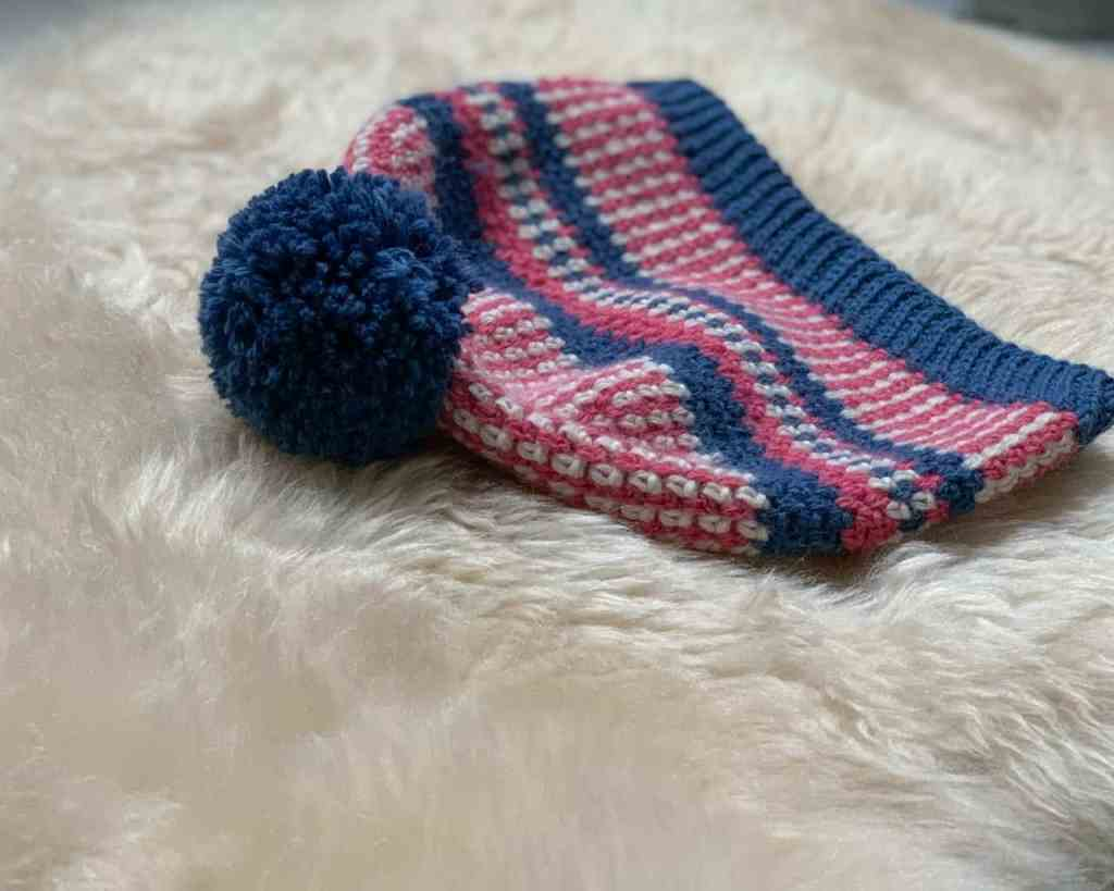 An angled view of the Scandinavian folk style crochet beanie hat focusing on the blue pom pom on top