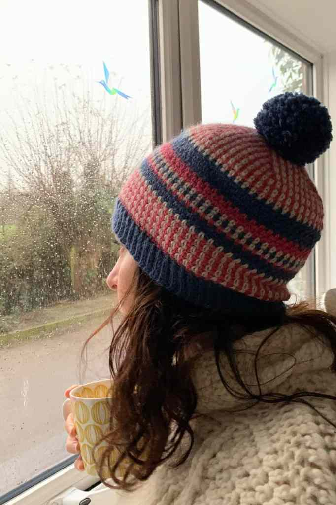 Dora is wearing the scandi stashbuster beanie hat in pink blue and cream as she stares out the window at the rain