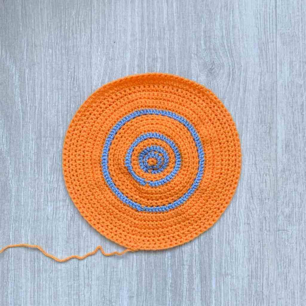 An unblocked orange crochet circle with pi increases shown in blue rounds lies on a grey wood background