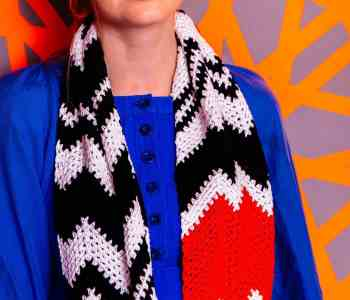 a black and white chevron crochet scarf with a pop off orange hangs round the neck of a woman in a blue dress
