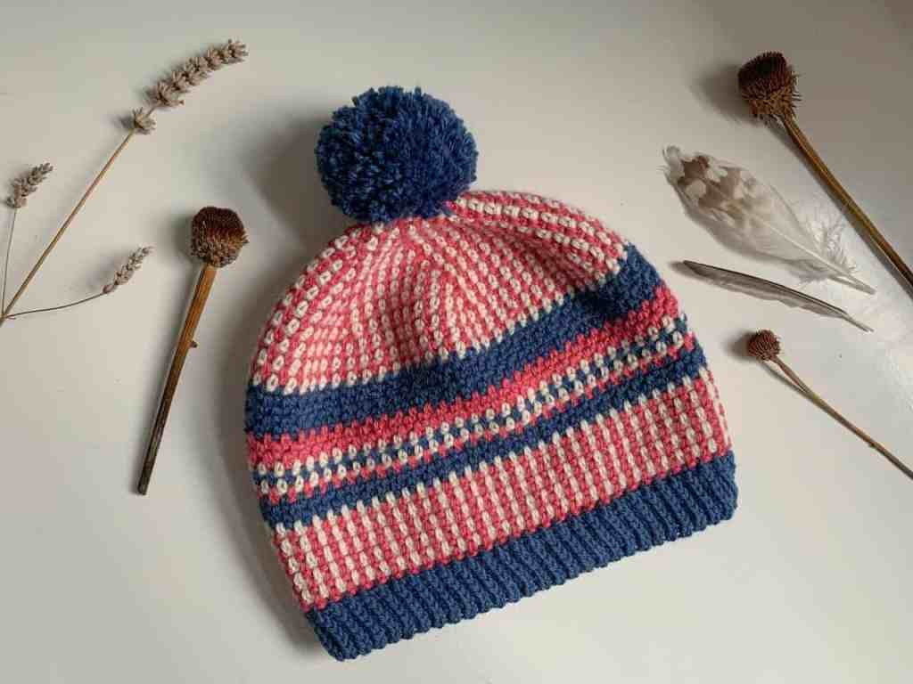 The scandi stashbusting beanie in pink cream and blue yarn, with a blue pom pom lays on a white surface with thistles and feathers framing it