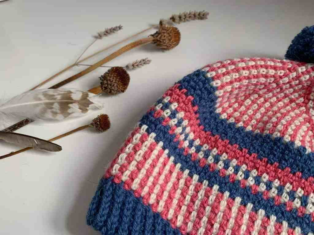 A close up of the crochet stitches in pink, cream and blue, that make up the scandi stashbuster beanie