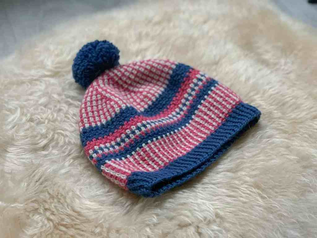 An angled view of the pink, blue and cream crochet Scandinavian style stashbusting beanie hat