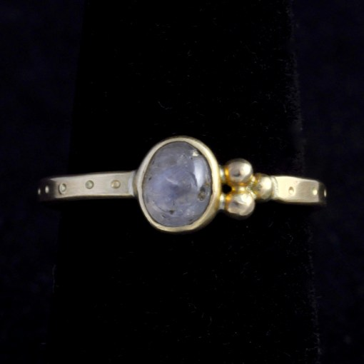 gold ring with central white sapphire and asymmetrical gold detail