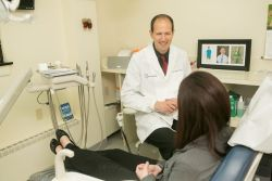 Dr. James Dores talking to a patient in the chair at Dores Dental in Longmeadow, MA