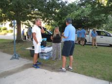 "Parents talk to the ""Blue Shirt"" volunteer as they wait with the boxes as their knob reports to the battalion."
