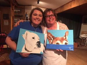 Mom and daughter holding painted canvas