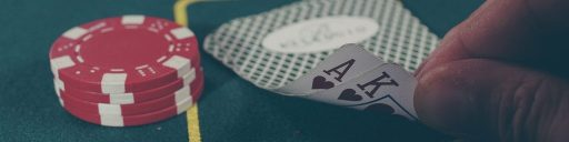 Card game trivia quiz. Image shows a stack of poker chips along with two cards showing the Ace and King of Hearts.