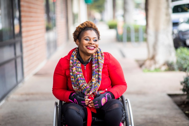 A young black disabled woman in a wheelchair.