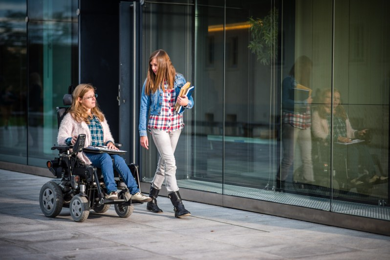 Disabled female student and her friend walking in campus, university building in background.
