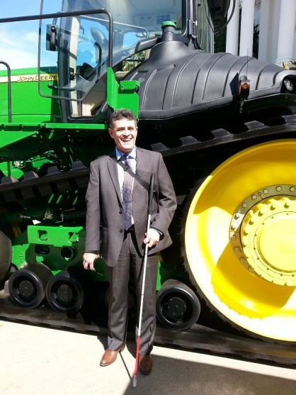Photo of Joe Xavier in front of a tractor.