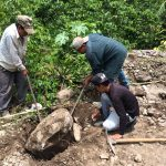 Construction teamwork, local Mayan workers moving a heavy rock
